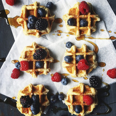 Overhead view of berry fruits and honey garnished on waffle at table