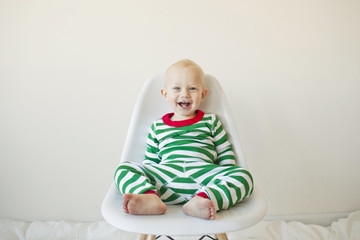 Portrait of baby boy sitting on chair against white background