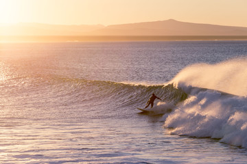 Man surfing in sea during sunset