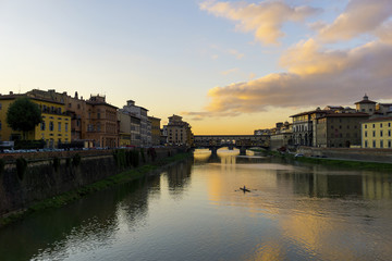 Ponte Vecchio over Arno river against sky during sunset in city