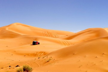 Desert car racing between sand dunes