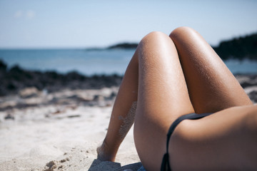 Low section of woman lying at beach on sunny day
