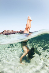 Woman doing handstand in sea