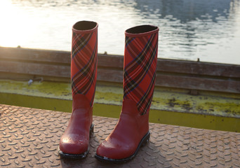 Red boots with tartan motive on the dock with river in background