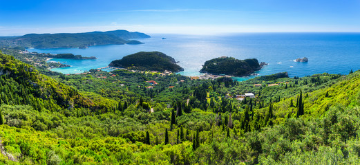 Beautiful summer panoramic seascape. View of the coastline into the sea bays with crystal clear azure water. In the backlight sunbeam light. Paleokastrica. Corfu. Ionian archipelago. Greece.