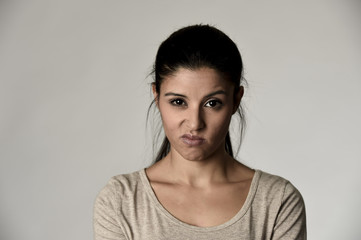 beautiful arrogant and moody hispanic woman showing negative feeling and contempt facial expression