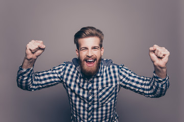 Excited happy young  bearded man triumphing with raised hands