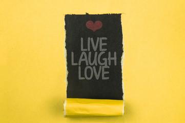 LIVE LAUGH LOVE. Words written under torn paper. Motivation concept text.