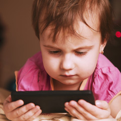 Little beautiful  girl with her smart phone (Development, educat
