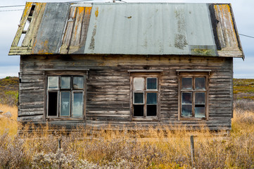 Old wooden decrepit house in need of repair with damaged roof and windows