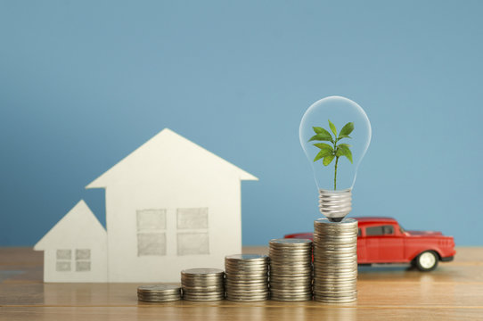 pile of money coins with small green tree, light bulb, toy car and  paper home,on wood and soft blue background, concept  in fiance, loan and buying