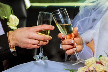 Womans and mans wedding hands with glasses.