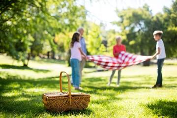 Family placing blanket in park