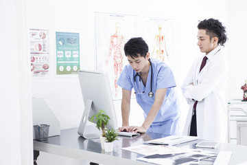 Two doctors are talking while watching a personal computer