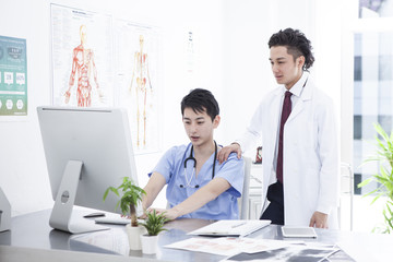 Two doctors are watching a computer together