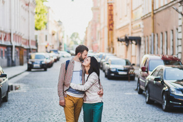 Young couple in casual style walking on city streets in old Saint-Petersburg