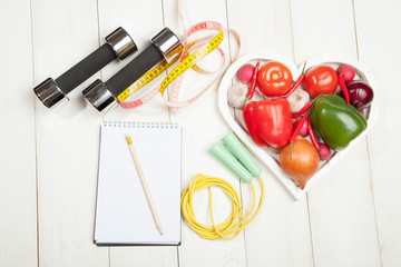 Sport and diet. Healthy lifestyle. Vegetables, dumbbells  notebook. Peppers, tomatoes, garlic, onion  radish in a heart on  white background