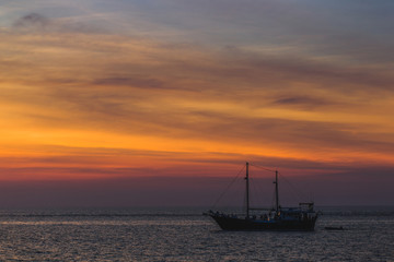 Big and vintage wooden pleasure sailboat in sea at sunset. Colorful sunset