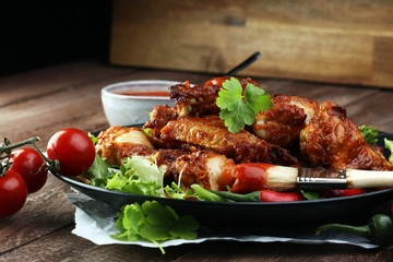 barbecue chicken wings close up on wooden tray with red spice sa