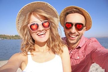 Young beautiful couple in sunglasses with hearts taking selfie on beach