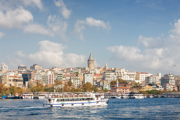 Sunny view of Bosphorus with excursion boats and Galata Tower, Istanbul, Turkey.