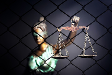 Lady Justice against cage background