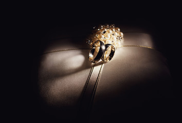 Wedding rings in the dark room on the pillow