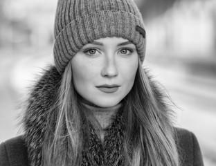 Black and white portrait of young woman at sunny winter day.