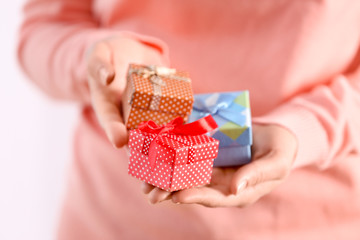 Female hands holding gift boxes, closeup
