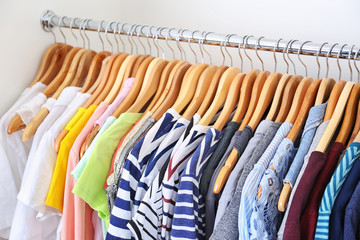 Hangers with colorful clothes on rack, closeup