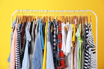 Hangers with colorful clothes on yellow background