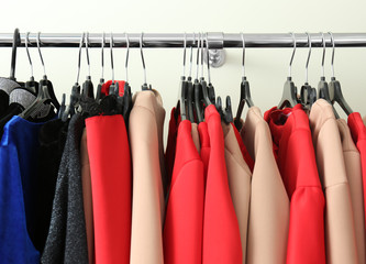 Rack with different clothes in modern shop, closeup