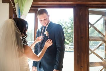 bride putting groom boutonniere