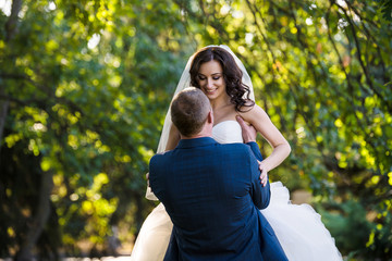 groom holds bride on arms