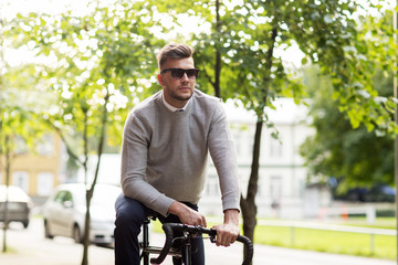 young man in shades riding bicycle on city street