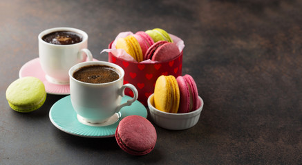 Colorful macaroons. Sweet macarons and cups of coffee on retro dark background with copy space. Selective focus. Holiday time concept