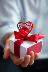 Close up shot man hands holding gift wrapped with red ribbon and heart. Small present in hands of human indoor. Selective focus on box. Holiday Valentine day concept