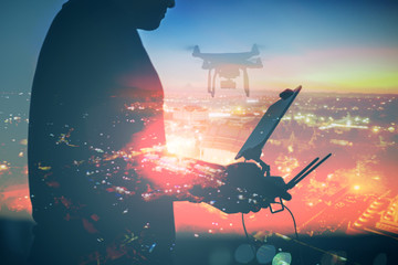 Man playing with the drone. Silhouette against the sunset sky and the cityscape background.