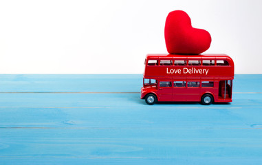 Love delivery on sightseeing bus with carrying red heart on roof for valentine's day and copy space for text. Valentine's day holiday concept.