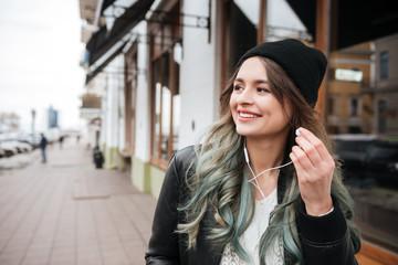 Woman wearing hat listening music with earphones.