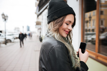 Smiling young woman wearing hat listening music with earphones.