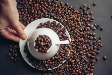 an inverted cup on a saucer with scattered coffee beans