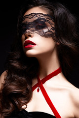 Young girl with a black lace mask on her face and a pendant in the form of heart on the neck. Beautiful model with bright make-up, red lips and curls. The picture on Valentine's Day.