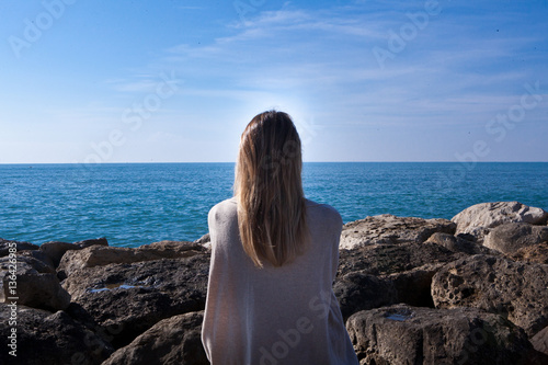 Donna Seduta Di Spalle Sugli Scogli Guarda Il Mare Stock Photo And