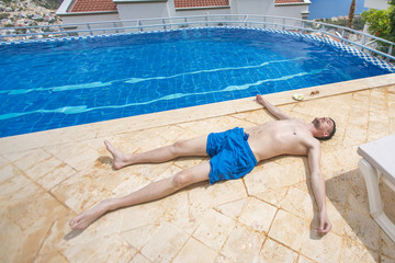 Man with the blue shorts lying on the tile around the pool