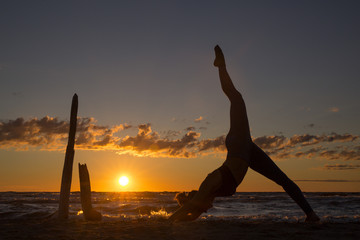Harmonious landscape with a woman practicing yoga by the sea at sunset.