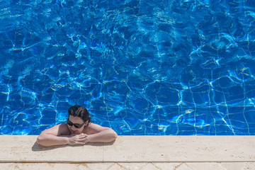 Woman in sunglasses near the pool edge, top view