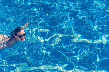 Brunette woman in bikini and sunglasses  swims in the pool