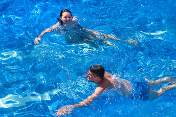 Couple man and woman swimming in the pool