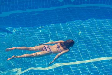Woman in a bikini  swimming in the pool